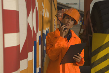 Mid adult woman using a walkie-talkie at a commercial dock