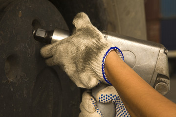 Close-up of a woman's hand tightening the bolt of a tire