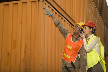 Male dock worker pointing with his hand and a female dock worker talking on a walkie-talkie beside him