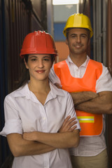 Portrait of two dock workers standing at a commercial dock and smiling