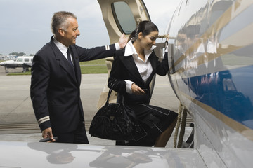 Cabin crew entering in a private airplane with a pilot standing behind her