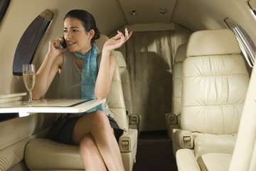 Businesswoman sitting in a private airplane and talking on a mobile phone