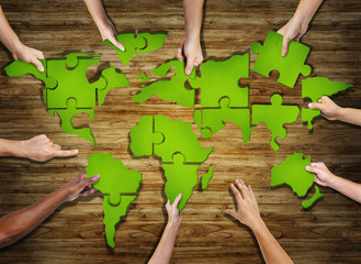 Group of Hands Holding Puzzle Forming World