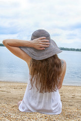 A female in a beach hat with a tattoo gazes out at the lake