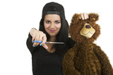 Beautiful young brunette ready to cut teddy bear with scissors