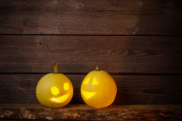 two yellow  pampkins on wooden background