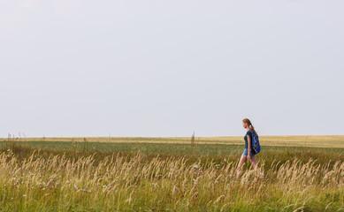 Beautiful young woman walking on a autumn field