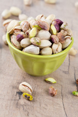 full bowl of pistachio on wooden surface