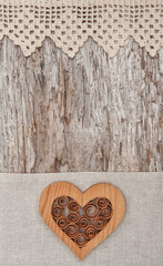 Wooden decorative heart on the lace fabric and old wood