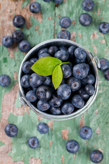 fresh blueberries in a bucket on wooden surface