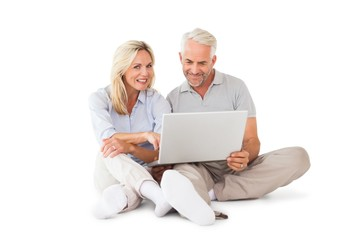 Happy couple sitting and using laptop