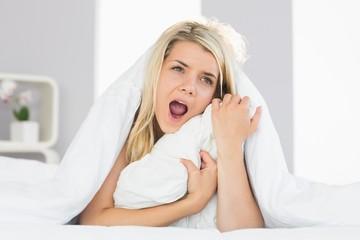 Sleepy woman yawning in bed