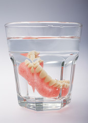 A set of dentures in a glass of water on a white background