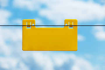 Blank yellow info plate hung on electric fence against blue sky