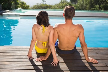 Rear view of couple sitting by swimming pool