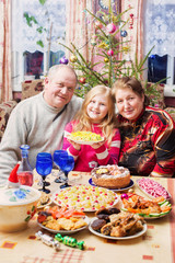 grandparents with little girl  sitting at festive table