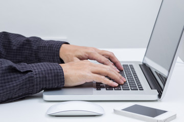 Man hands typing on laptop computer