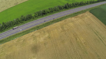 Wheat fields and  highway with cars. Aerial top view