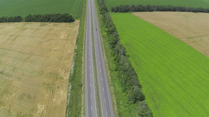 Green and yellow fields and highway. Aerial top view