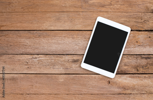 Tablet computer on old wooden background - 69367744