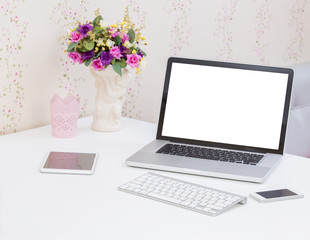 Blank screen laptop computer with accessories on the table