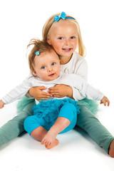 Preschool girl holding infant girl