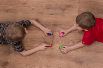 Two brothers playing on floor at home.