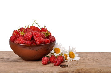 Raspberries in a bowl on a wooden table on a white background