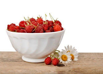Ripe raspberries in a bowl on a wooden table on a white backgrou