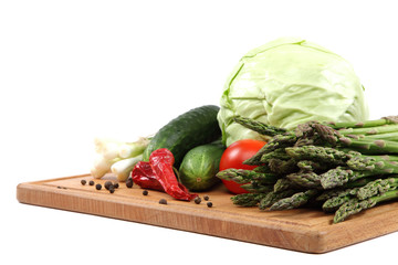 Fresh vegetables on a wooden cutting board.