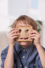 portrait of funny boy playing with bread.