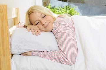 Frau im Schlafanzug schläft im Bett