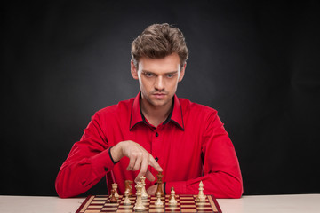 Young casual man sitting over chess.