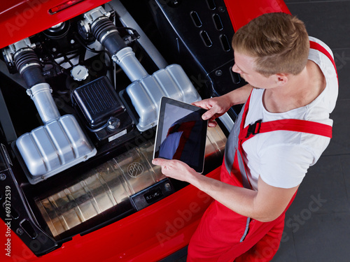 canvas print picture Mechanic inspecting the engine of a car with touchpad