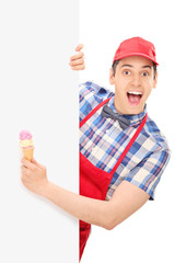 Excited male ice cream vendor posing behind a panel