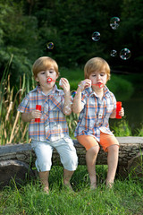 Twin Brothers Blowing Soap Bubbles in Summer Park