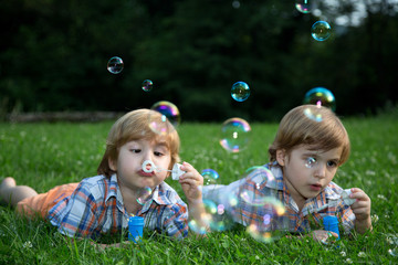 Twin Brothers  Blowing Soap Bubbles on Grass in Summer Park