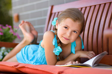 Little girl is reading a book