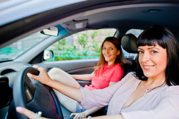 Two young and beautiful woman sitting in the car