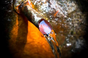 Wasserstrahl aus Eisenrohr im Felsen