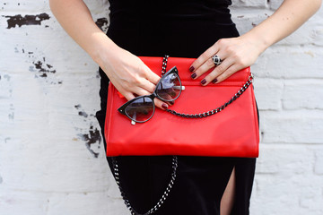 Fashionable woman with  stylish red clutch and sunglasses
