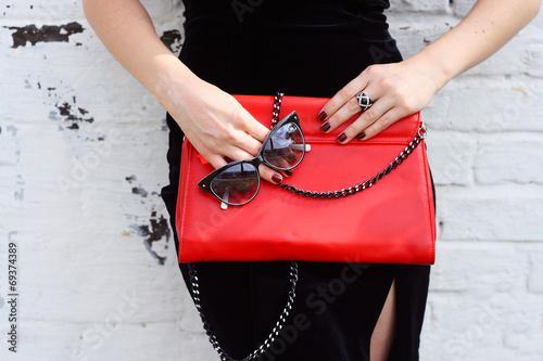 Leinwandbild Motiv Fashionable woman with  stylish red clutch and sunglasses