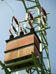 High voltage transformer on green metal pylon
