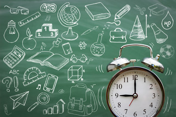 Alarm clock over blackboard