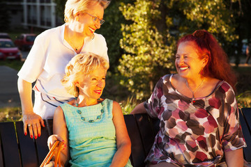 Three elderly ladies sitting on a bench and have fun