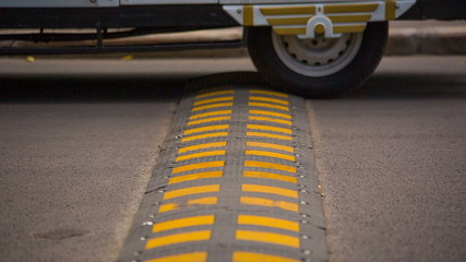 Wheels and Speed Bump on the Road. HD 1080p.