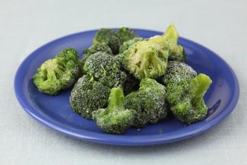 Frozen broccoli on a purple plate