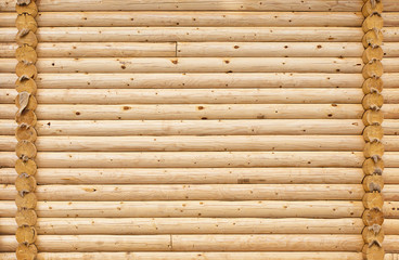 Wall of the house of round wooden logs.