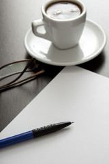 coffee, white paper and pen