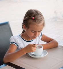 Little girl is drinking from cup of cocoa at  outdoor cafe